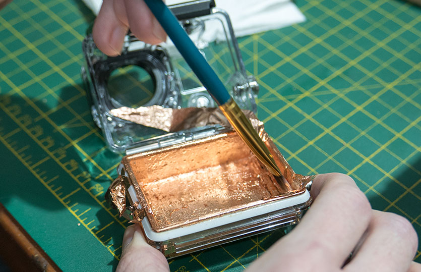 Applying the copper leaf to the back panel on the waterproof case